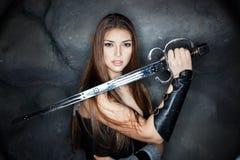 美丽的女孩在他的手上的拿着钢剑 免版税库存图片