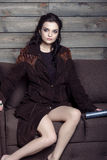 美丽的女孩坐一个长沙发在乡间别墅里 库存图片