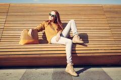 美丽的女孩坐一条长凳在一个温暖的夏日 免版税库存图片