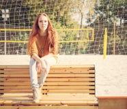 美丽的女孩坐一条长凳在一个温暖的夏日 库存图片
