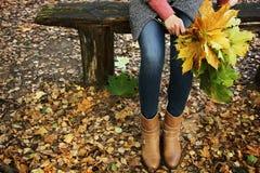 年轻美丽的女孩坐一条长凳在公园,并且拿着下落的槭树花束离开 图库摄影