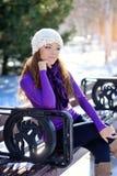 美丽的女孩坐一条长凳在冬天 库存图片