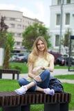 年轻美丽的女孩坐一条长凳在夏天公园 图库摄影
