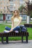 年轻美丽的女孩坐一条长凳在夏天公园 库存照片