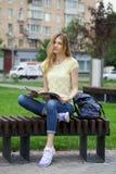 年轻美丽的女孩坐一条长凳在夏天公园 库存图片