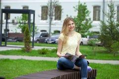 年轻美丽的女孩坐一条长凳在夏天公园 免版税库存图片