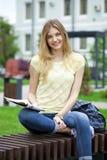年轻美丽的女孩坐一条长凳在夏天公园 免版税库存照片