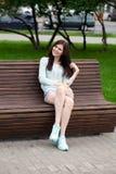 年轻美丽的女孩坐一条长凳在夏天公园 免版税图库摄影
