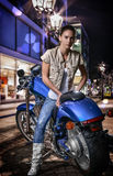 美丽的女孩坐一辆蓝色摩托车,在夜背景的城市街道 库存图片