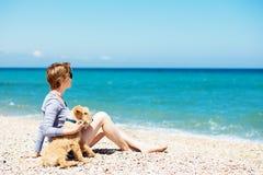 美丽的女孩坐与狗狗的海滩 免版税库存图片