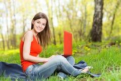 美丽的女孩坐与笔记本的草 库存图片