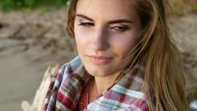 年轻美丽的女孩坐保护了格子花呢披肩享受日落的河边 股票视频