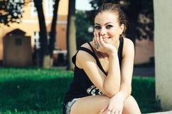 美丽的女孩坐台阶和 图库摄影