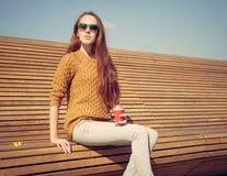 美丽的女孩坐在咖啡一温暖的夏日whis cuo的一条长凳  免版税库存图片