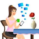 美丽的女孩坐在桌,饮用的茶上,并且反应m 免版税库存图片