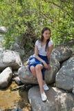 年轻美丽的女孩坐在河岸的一个岩石 免版税图库摄影
