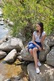 年轻美丽的女孩坐在河岸的一个岩石 免版税库存照片