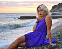 美丽的女孩坐在的海滩一件轻的丝绸礼服 免版税图库摄影