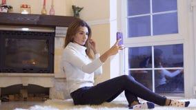 美丽的女孩坐地板并且做selfie在智能手机 影视素材