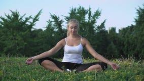 年轻美丽的女孩坐小山,思考和享用太阳 股票视频