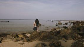 美丽的女孩坐岩石在海岸附近并且调查距离 股票视频