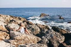 美丽的女孩坐岩石海滨 库存照片