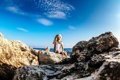 美丽的女孩坐岩石海滨 免版税库存照片