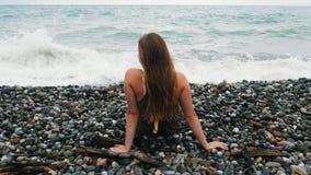 美丽的女孩坐岩石,调直她的头发并且享受刷新的微风和美丽的景色  股票录像