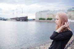 年轻美丽的女孩坐岸和调直头发 在背景中是被弄脏的老船 库存照片