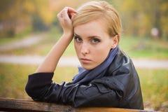 美丽的女孩坐年轻人 库存照片