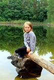 美丽的女孩坐日志由河 免版税库存图片