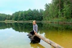 美丽的女孩坐日志由河 免版税库存照片