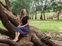 美丽的女孩坐树 库存照片