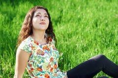 美丽的女孩坐森林、明亮的太阳和阴影的一块沼地在草 免版税库存照片