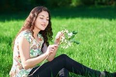 美丽的女孩坐森林、明亮的太阳和阴影的一块沼地在草 免版税库存图片