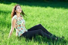 美丽的女孩坐森林、明亮的太阳和阴影的一块沼地在草 库存图片