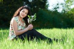 美丽的女孩坐森林、明亮的太阳和阴影的一块沼地在草 免版税图库摄影
