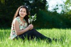 美丽的女孩坐森林、明亮的太阳和阴影的一块沼地在草 图库摄影