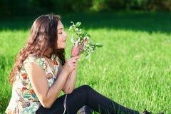 美丽的女孩坐森林、明亮的太阳和阴影的一块沼地在草 库存照片