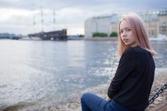 年轻美丽的女孩坐江边和看照相机 在背景中是被弄脏的老船 库存照片