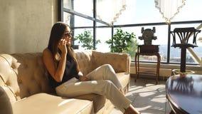 美丽的女孩坐沙发和谈话在电话 影视素材