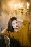 美丽的女孩坐的沙发 图库摄影
