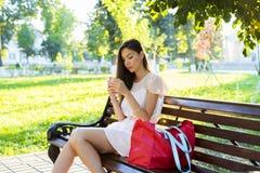 美丽的女孩坐的长凳,深色的桃红色礼服,时尚与您的电话的生活方式在社交写一则消息 库存照片