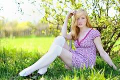 美丽的女孩坐草甸 免版税库存照片