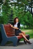 美丽的女孩坐长凳在公园 免版税库存图片