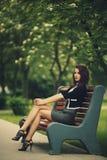 年轻美丽的女孩坐长凳 库存照片