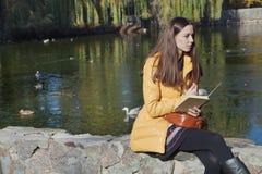 美丽的女孩学生坐栏杆在太阳的城市池塘附近 免版税库存图片