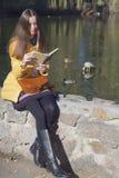 美丽的女孩学生坐栏杆在太阳的城市池塘附近 库存照片