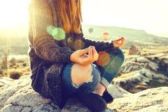 年轻美丽的女孩实践的瑜伽在一座山顶部在日出的卡帕多细亚 放松实践  免版税库存照片
