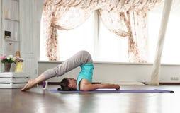 年轻美丽的女孩实践的瑜伽在家 免版税库存照片